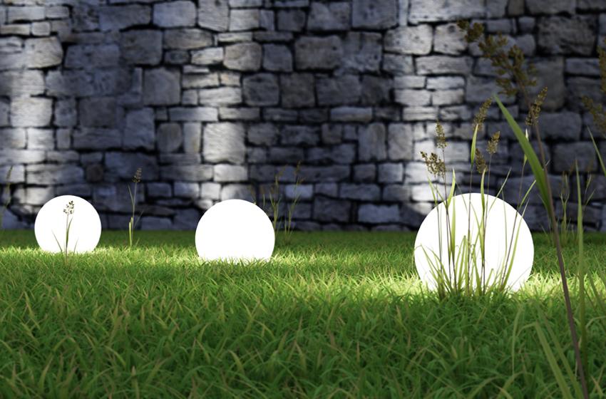 weiße Gartenbeleuchtung vor Steinmauer